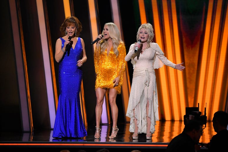 Hosts Reba McEntire, from left, Carrie Underwood and Dolly Parton appear at the 53rd annual CMA Awards at Bridgestone Arena, Wednesday, Nov. 13, 2019, in Nashville, Tenn.