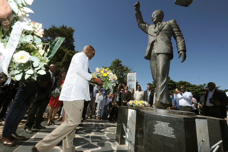 Wreaths are laid at a statue of former President Nelson Mandela at the entrance to the Victor Verster prison in Paarl, South Africa, Tuesday, Feb. 11, 2020.