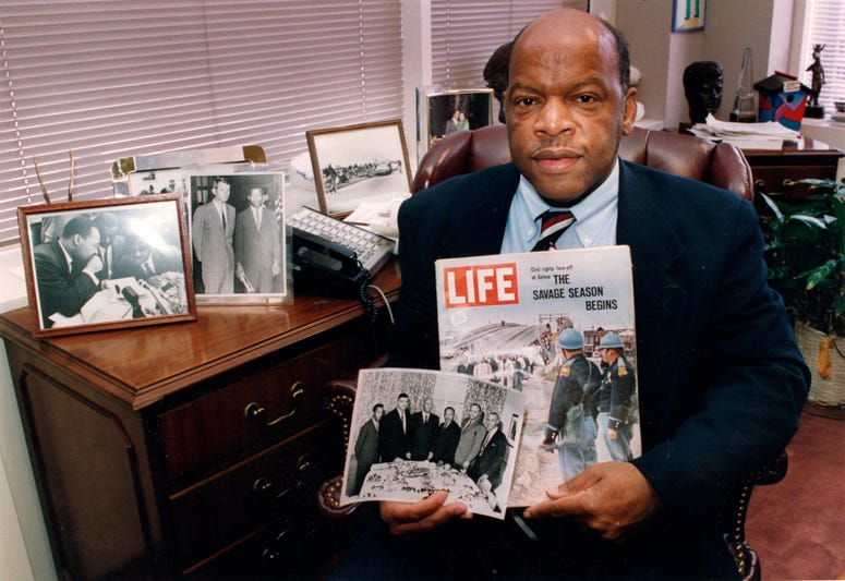 Congressman John Lewis poses in his Atlanta office with two of his favorite items from his collection of memorabilia from his younger days as a civil rights activist in the 1960s.