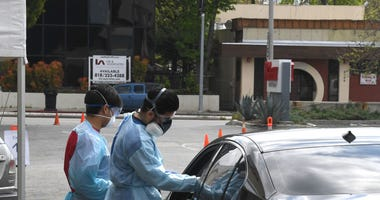 Workers wearing personal protective equipment gather the tests administered from people's cars as Mend Urgent Care hosts a drive-thru testing.