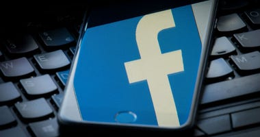 The logo of social networking site Facebook is reflected on the screen of a smartphone resting on a laptop keyboard.