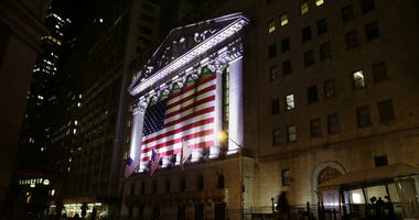 FILE- In this Feb. 17, 2017, file photo, an American flag hangs on the front of the New York Stock Exchange in New York.