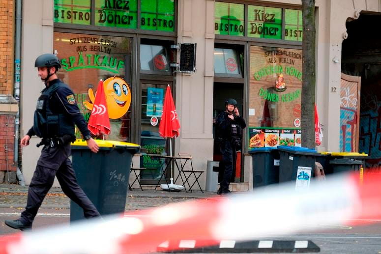 A police officer walks in front of a kebab grill in Halle, Germany.