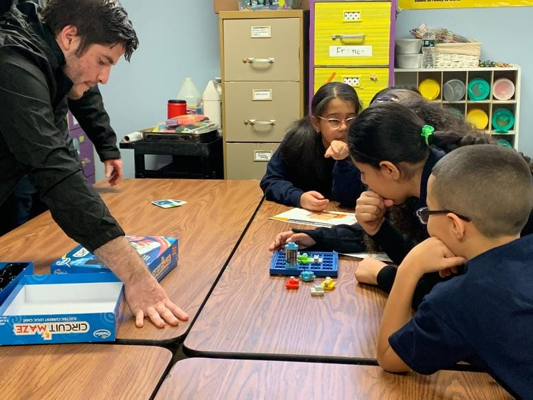 Students at St. Joseph Pro-Cathedral School play with robots and coding games.