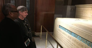 Sister Donna Breslin (front) president of the Sisters of the Blessed Sacrament, examines the newly installed tomb of St. Katharine Drexel in the Cathedral Basilica of Saints Peter and Paul, next to Sister Jane Nesmith, the order's vice president.
