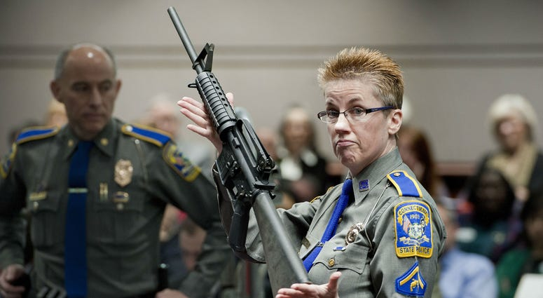 In this Jan. 28, 2013, file photo, firearms training unit Detective Barbara J. Mattson, of the Connecticut State Police, holds a Bushmaster AR-15 rifle.