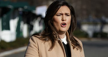 White House press secretary Sarah Huckabee Sanders talks with reporters outside the White House, Tuesday, Dec. 18, 2018, in Washington.