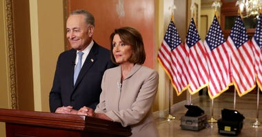 Senate Minority Leader Charles Schumer (D-NY) and Speaker of the House Nancy Pelosi (D-CA) pose for photographs after delivering a televised response to President Donald Trump's national address about border security at the U.S. Capitol.