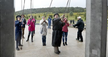 Members of passenger families, friends and volunteer repesentatives pull the ropes to ring the chimes at the dedication of the 93-foot tall Tower of Voices on Sunday, Sept. 9, 2018 at the Flight 93 National Memorial in Shanksville, Pa.