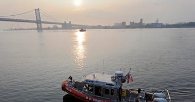 A U.S. Coast Guard boat cruises the Delaware River at Penn's Landing.