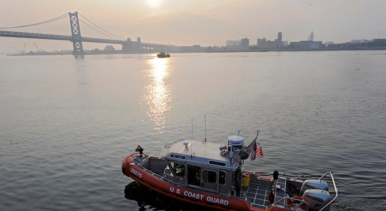 A U.S. Coast Guard boat cruises the Delaware River at Penn's Landing.