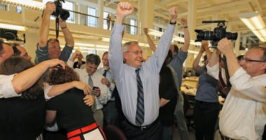 Members of the Philadelphia Inquirer staff react to learning of their Pulitzer Prize for Public Service from their series on School Violence, Monday, April 16, 2012. Editor Stan Wischnowski, center, raises his hands in celebration.