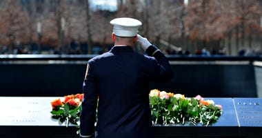 A member of FDNY salutes after placing a flower at the 9/11 Memorial during a ceremony commemorating the 23rd anniversary of the 1993 World Trade Center bombing, in New York, the United States, Feb. 26, 2016.