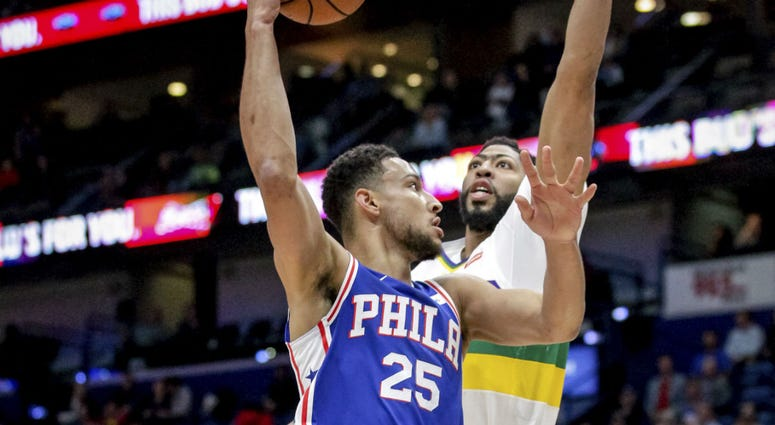 Philadelphia 76ers guard Ben Simmons (25) shoots against New Orleans Pelicans forward Anthony Davis (23) in the first half of an NBA basketball game in New Orleans, Monday, Feb. 25, 2019.
