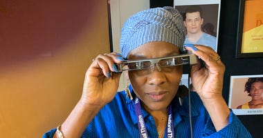 """Cheryl Johnson, West Philadelphia, who suffers from hearing loss, puts on her smart caption glasses which she described as """"amazing"""" in helping her to follow the performance of """"Dot"""" at People's Light in Malvern, Chester County."""