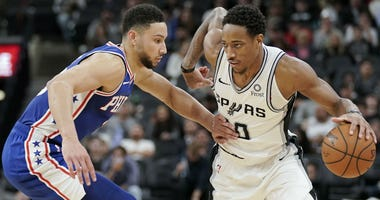 San Antonio Spurs' DeMar DeRozan, right, drives against Philadelphia 76ers' Ben Simmons during the second half of an NBA basketball game, Monday, Dec. 17, 2018, in San Antonio.