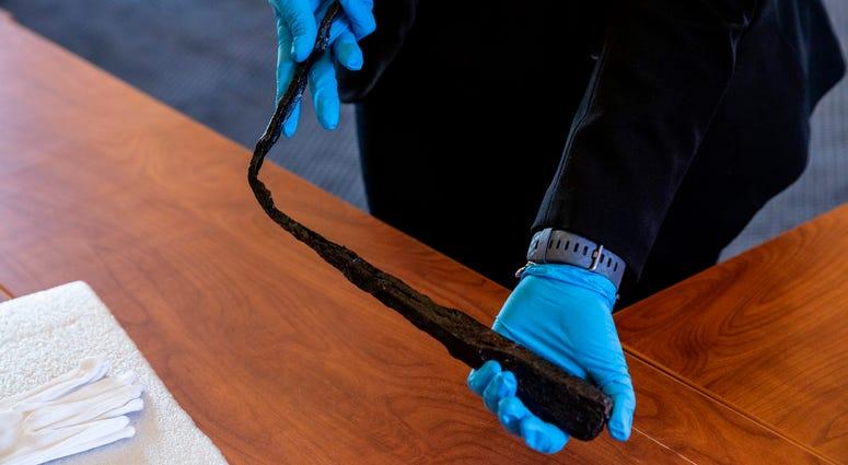 Inventors look at one of Benjamin Franklin's bent lightening rods at the Franklin Institute.