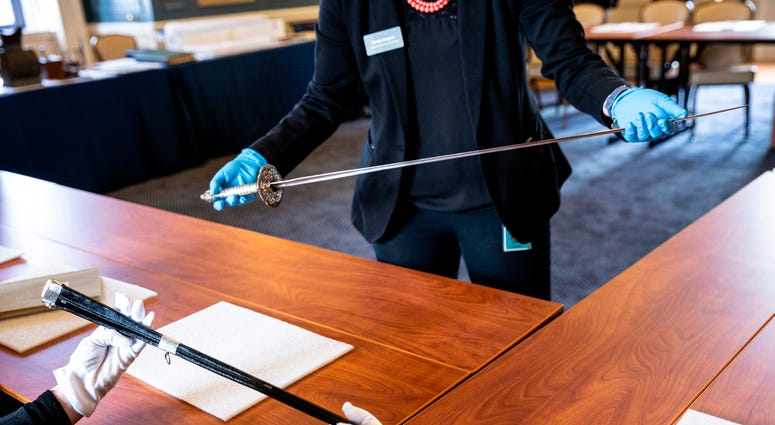 Inventors marvel at Benjamin Franklin's ceremonial sword at the Franklin Institute.