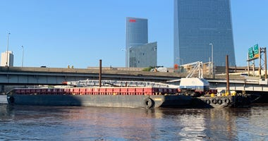 The barge used in the Schuylkill River dredging project has become wedged under the I-676 overpass.