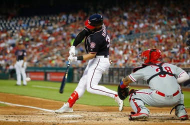 Washington Nationals' Bryce Harper, left, hits a two-run home run off Philadelphia Phillies starting pitcher Nick Pivetta (not shown) during the second inning of a baseball game at Nationals Park.