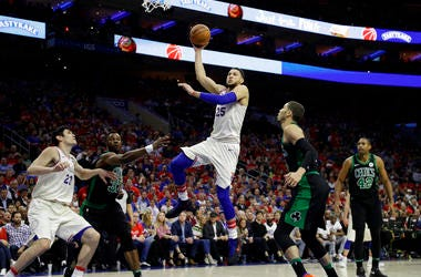 Philadelphia 76ers' Ben Simmons (25) goes up for a shot between Boston Celtics' Semi Ojeleye (37) and Jayson Tatum (0).