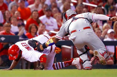St. Louis Cardinals' Dexter Fowler, left, is tagged out by Philadelphia Phillies catcher Jorge Alfaro after being caught between third and home during the seventh inning.
