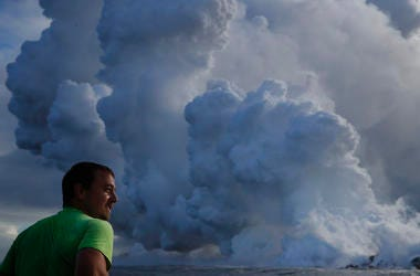 Joe Kekedi watches as lava enters the ocean, generating plumes of steam.