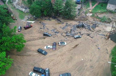 Vehicles swept by floodwater near the intersection of Ellicott Mills Drive and Main Street in Ellicott City, Md.