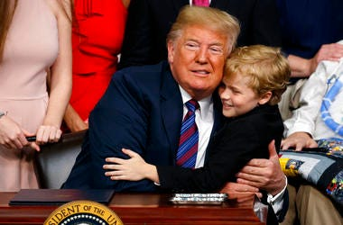 "President Donald Trump hugs Duchenne Muscular Dystrophy patient Jordan McLinn after signing the ""Right to Try"" act in the South Court Auditorium on the White House campus."