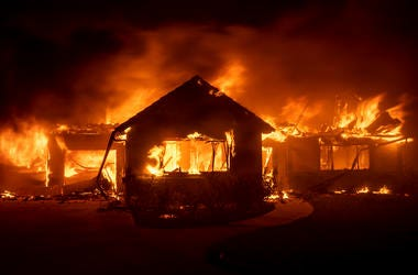 Flames from the Hillside Fire consume a home in San Bernardino, Ca.