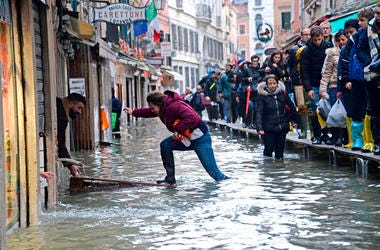 A woman tries to cross a flooded street as people walk on a trestle bridge during high water, in Venice, northern Italy, Friday, Nov. 15, 2019.