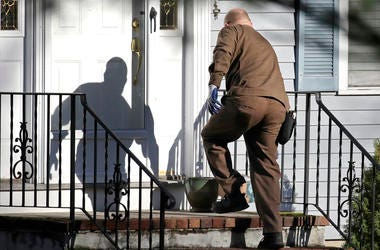 A UPS driver delivers an Amazon package to a residence in North Andover, Mass.