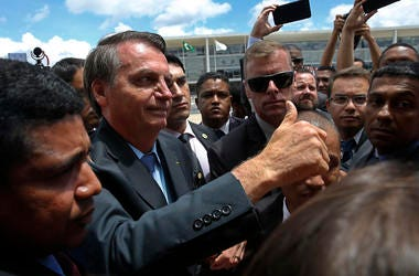 Brazil's President Jair Bolsonaro flashes a thumbs up as he greets supporters after attending a Changing of the Guard at the Planalto Presidential Palace, in Brasilia, Brazil, Thursday, Nov. 28, 2019.