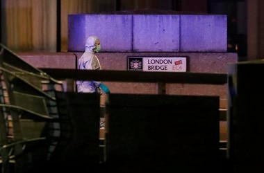 A police forensic officer walks by a sign where a man was shot dead by police on London Bridge following an incident in London.
