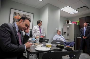 Attorney Adam Slater, left, checks his phone during a working lunch with lawyers in his firm.