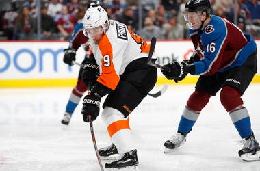 Philadelphia Flyers defenseman Ivan Provorov, left, fires the puck on the net after slipping pst Colorado Avalanche defenseman Nikita Zadorov in the second period of an NHL hockey game Wednesday, Dec. 11, 2019, in Denver.