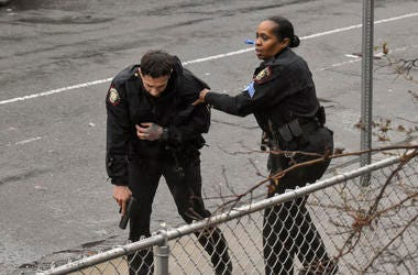 Jersey City police Sgt. Marjorie Jordan, right, helps fellow officer Raymond Sanchez to safety after he was shot during a gunfight that left multiple dead in Jersey City, N.J.