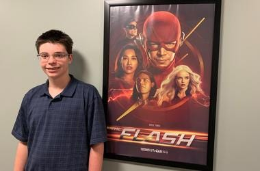 "Michael stands next to a promotional poster for his favorite TV show, ""The Flash,"" at the KYW broadcast center."