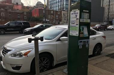 A Center City parking kiosk next to the remains of an old meter stand.
