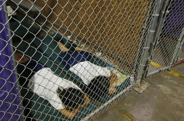 two female detainees sleep in a holding cell