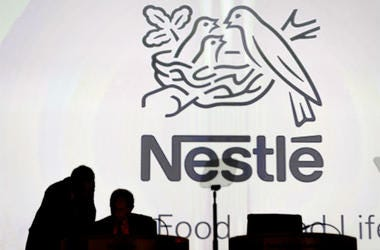 Nestle's directors speak in front of the Nestle's logo