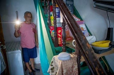 Using a cell phone for a flash light, Jose Manuel Torres, 60, made his way to the small room where he now uses as a home as the rest of his home is being fixed after it was destroyed more than seven months ago by Hurricane Maria.