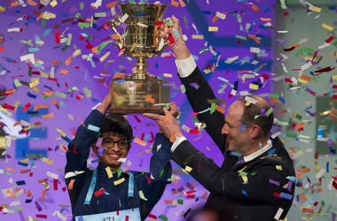 Karthik Nemmani, 14, from McKinney, Texas, is presented with the Scripps National Spelling Bee trophy