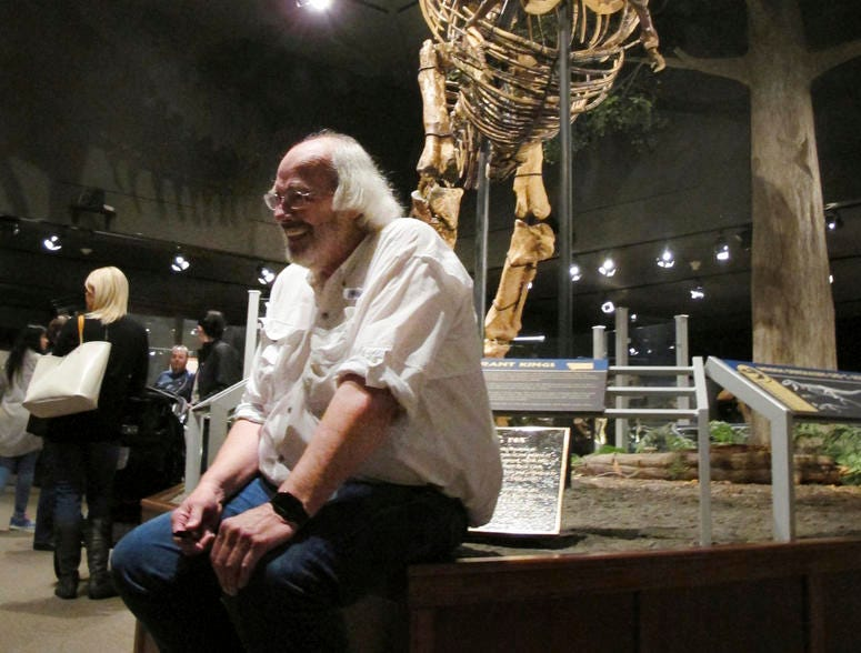 Jack Horner sits under Montana's T-Rex in the Museum of the Rockies in Bozeman, Mont.
