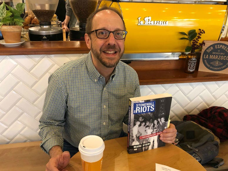 "Historian Marc Stein is shown with his book ""The Stonewall Riots: A Documentary History."""
