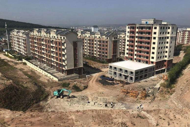 In this Sept. 12, 2018, photo, paleontologist Xu Xing leads a dig site, foreground, next to new apartments being constructed in Yanji, China.