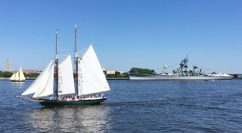 The battleship USS New Jersey, seen in the background, fired off rounds during the Parade of Sail.