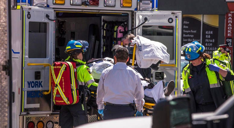 A injured person is put into the back of an ambulance in Toronto after a van mounted a sidewalk crashing into a crowd of pedestrians.