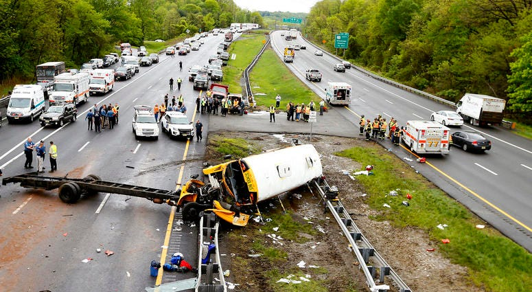 Emergency personnel examine a school bus after it collided with a dump truck, injuring multiple people, on Interstate 80 in Mount Olive, N.J.
