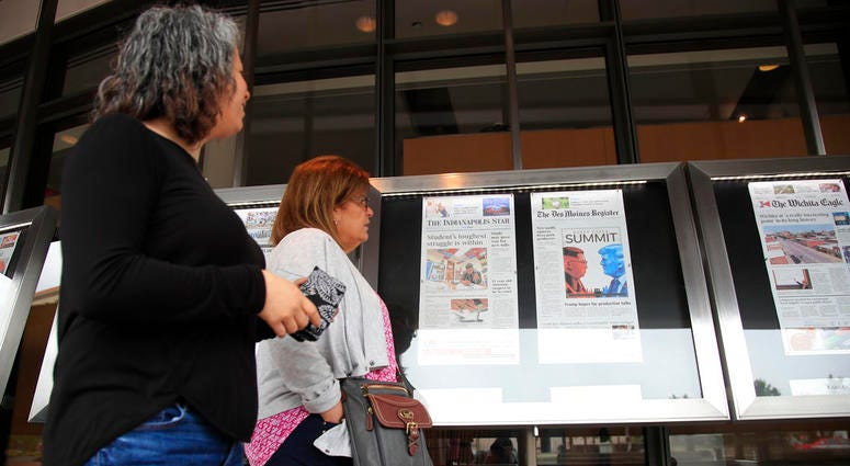 Newseum visitors browse newspaper front pages displayed outside the museum in Washington.